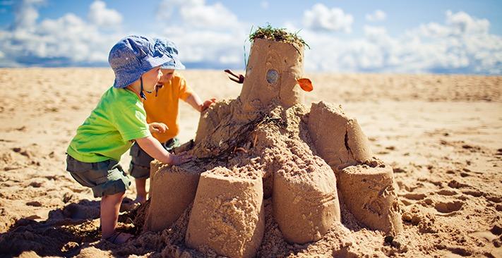 children-on-beach-sandcastle