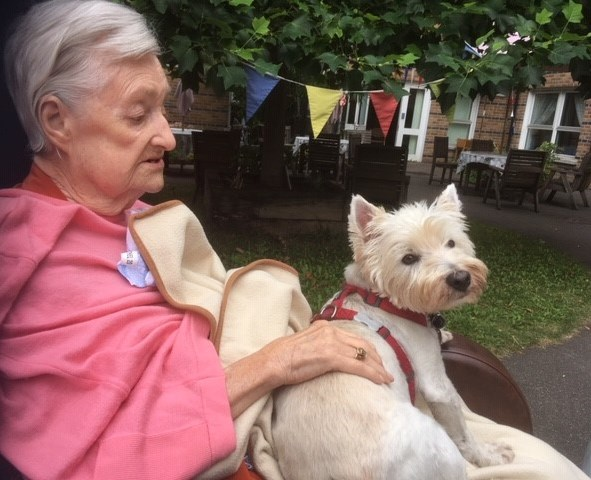 An elderly lady with her Yorkshire terrier on her lap who cinnamon trust support.